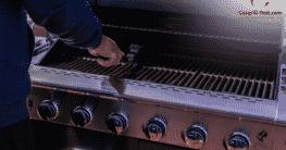 Mann reinigt und bereitet Gasgrill auf die neue Grillsaison vor.